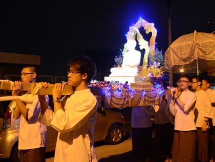 Carrying the Sedan symbolizes upholding the Buddha-Dhamma with faith and devotion.